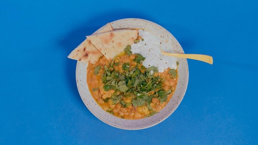 Un bol de curry de pois chiches avec de la coriandre, sauce blanche et pain naan.
