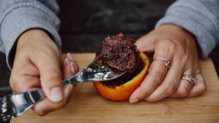 Sur une planche en bois, est déposé le gâteau au chocolat dans une orange.  Une des mains de Geneviève tient l'orange et l'autre tient une cuillère. Sur la cuillère, il y a un morceau de gâteau.