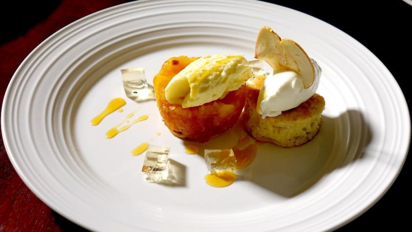 Un morceaux de gâteau dans une assiette avec de la mousse aux pommes et de la sauce au caramel.
