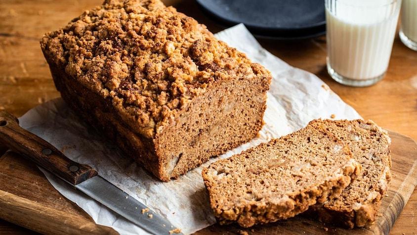 Un gâteau streusel à la poire avec une tranche déjà coupée.