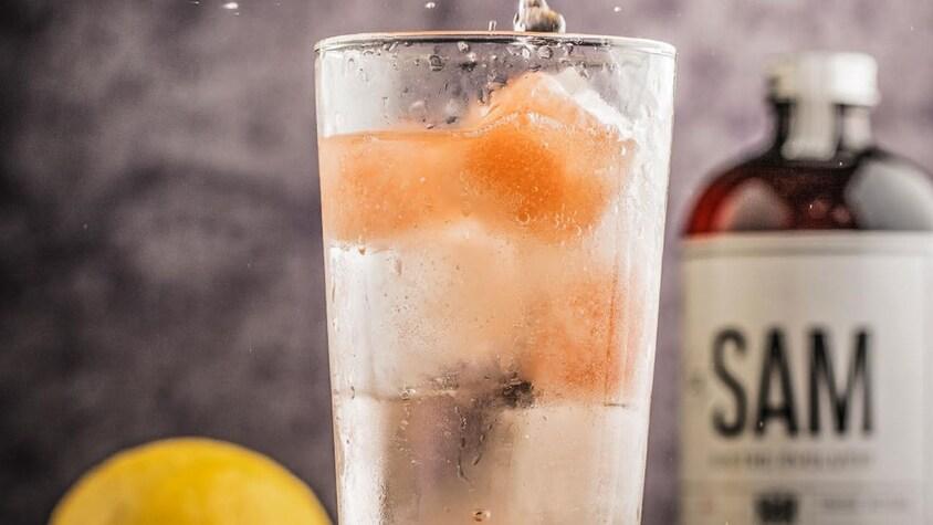 Un verre de gin tonic avec des glaçons colorés.