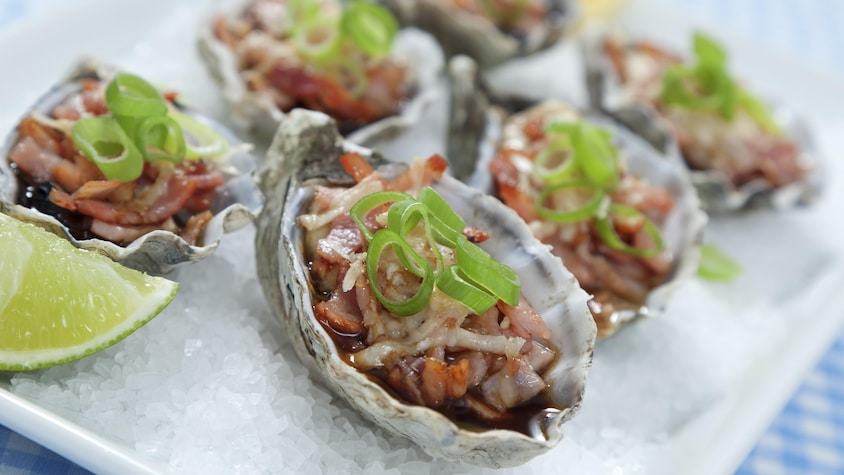 Six huîtres bien garnies prêtes à être dégustées.