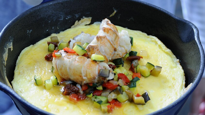 Une poêle en fonte avec une omelette aux langoustines et ratatouille.