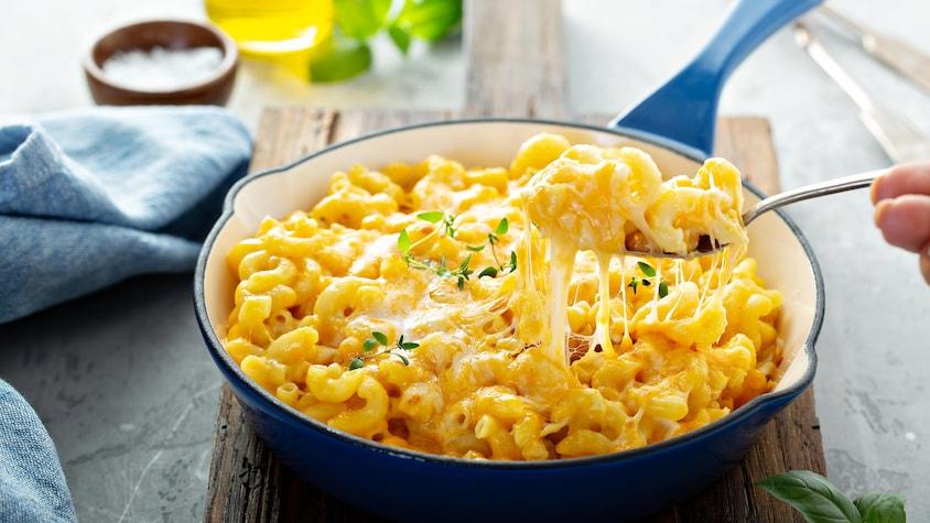 Un poêlon rempli de macaroni au fromage et aux tomates.