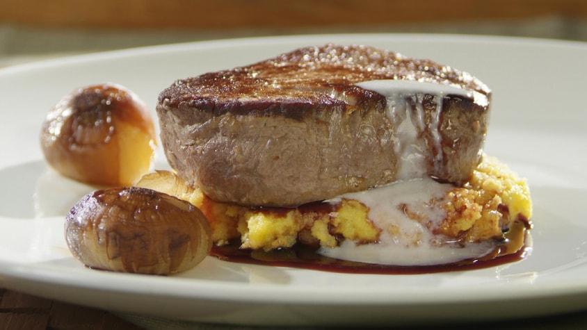 Médaillon de filet de boeuf, sauce au vin rouge, fondu de parmesan dans une assiette.