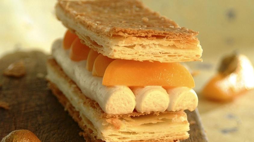 Un millefeuille garni de quartiers d'abricots et de trois boudins de crème au centre.