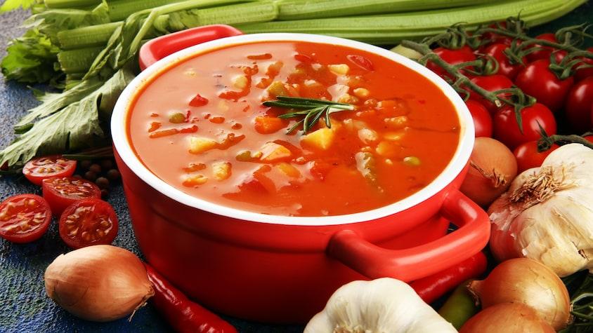 Un bol rempli de soupe minestrone et entouré de plusieurs légumes.