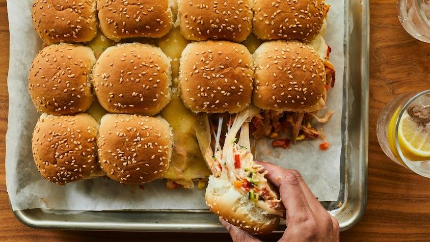 Une plaque de cuisson contenant des minis sandwichs au poulet Buffalo, est déposée sur un comptoir en bois.