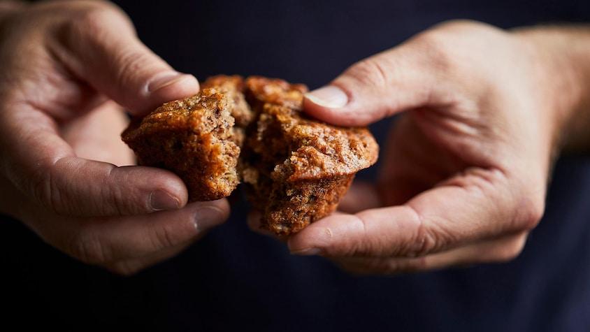 Mains séparant un muffin au bananes en deux.