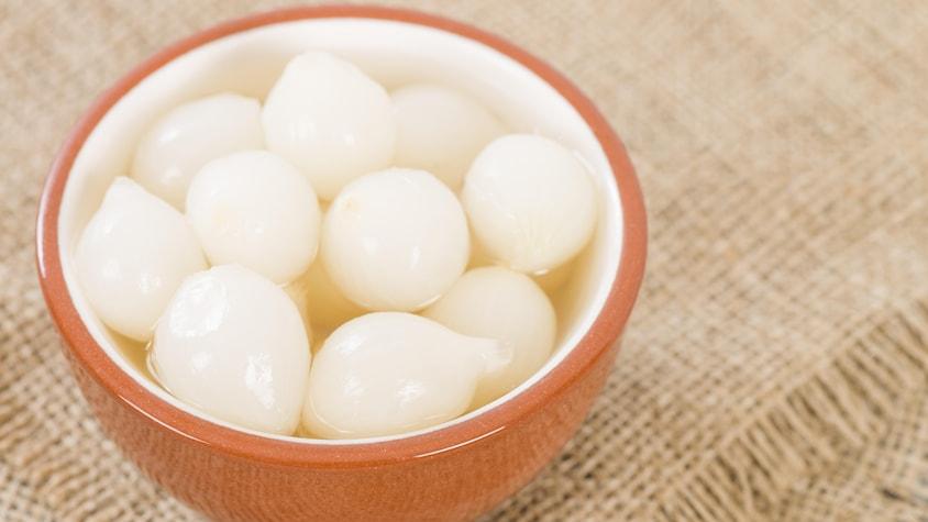 Un petit bol rempli d'oignons perlés marinés.