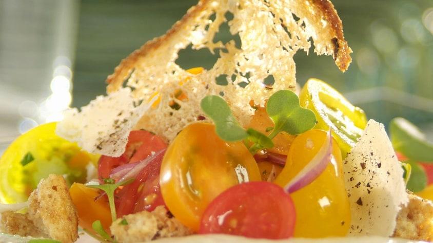 Panzanella aux tomates cerises mélangées sur une assiette.