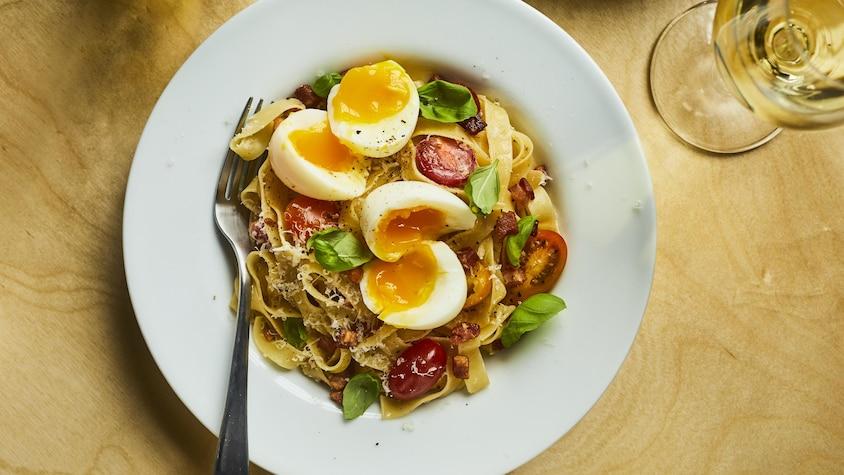Bol de pappardelles avec tomates cerises, œufs mollets et basilic.