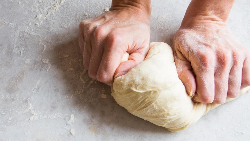 Des mains qui pétrissent de la pâte à pizza.