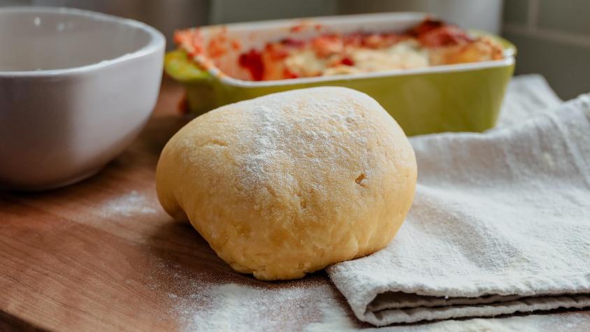 Une boule de pâte farinée, prête à être transformée en pâtes fraîches aux oeufs.