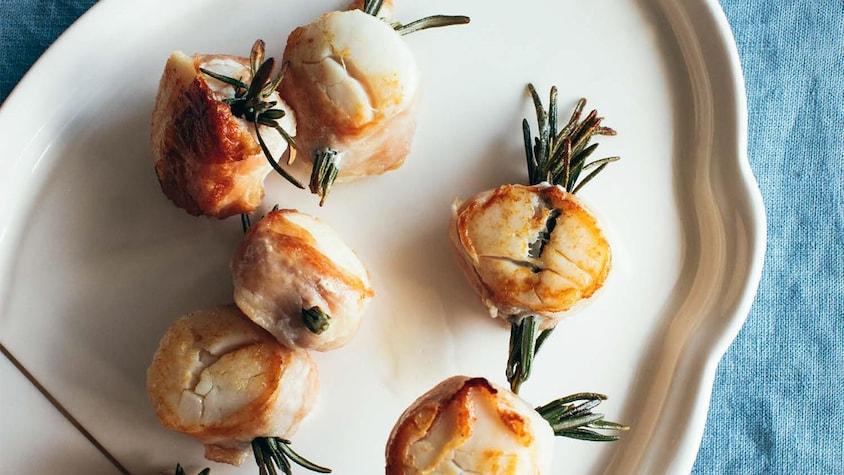 Une assiette avec de pétoncles entourées de prosciutto retenu par des branches de romarin.