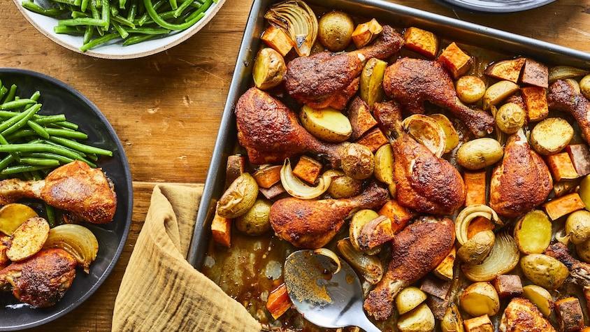 Sur une table en bois, est déposé une plaque à cuisson remplie de pilons de poulet BBQ.