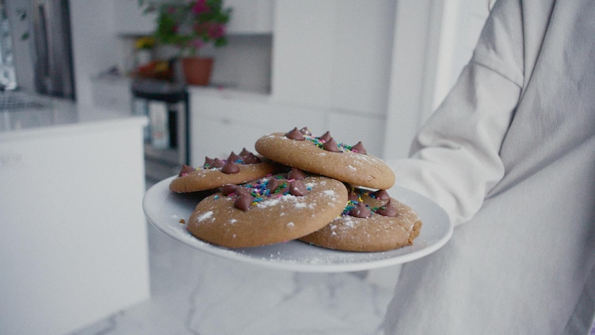 Quatre biscuits à la mélasse avec pépites de chocolat et bonbons dans une assiette blanche.