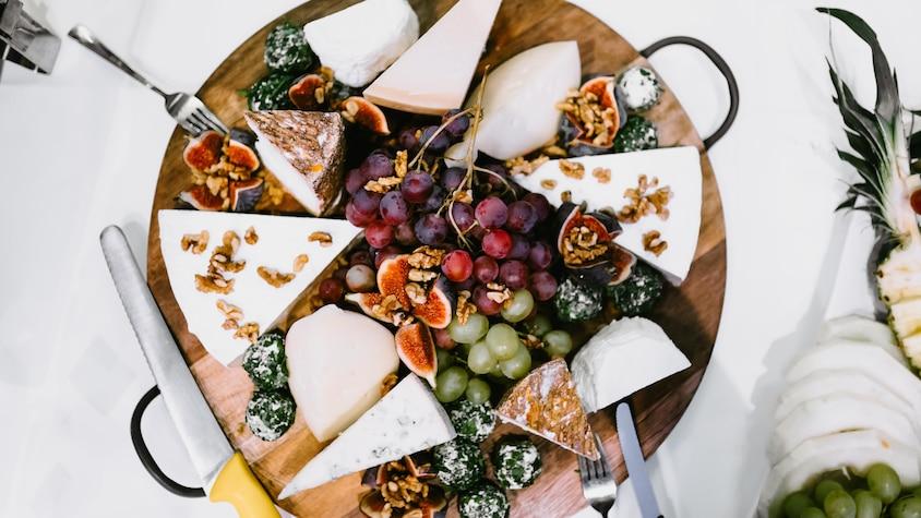 Un plateau rempli de fromages, de fruits et de noix.