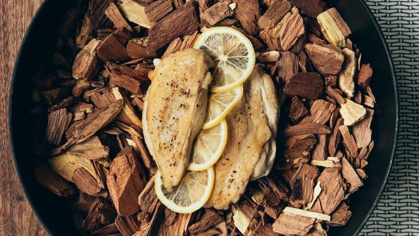 Dans une cocotte en fonte, des poitrines de poulet grillée sur copeaux de bois et garnies de tranches de citron.