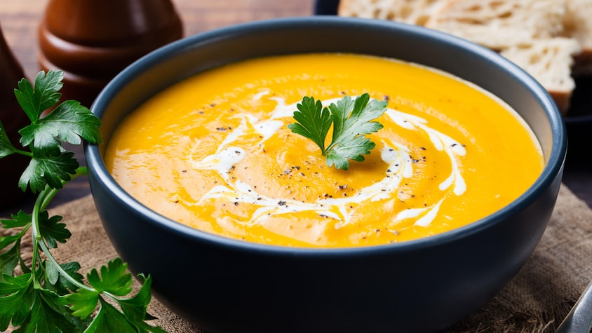 Une soupe de patates douces et de carottes avec un brin de coriandre sur le dessus.