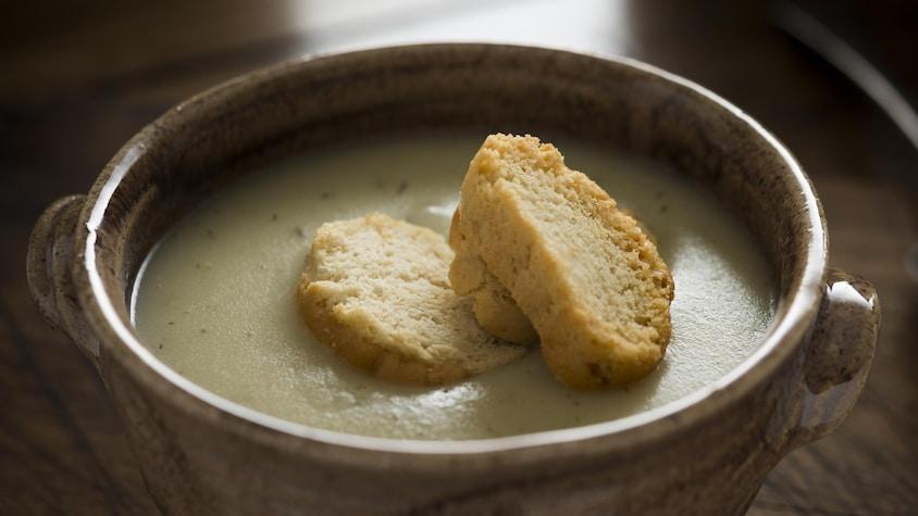 Un bol rempli de potage avec trois croûtons sur le dessus.