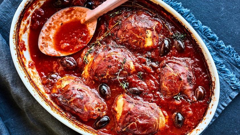 Un plat de poulet braisé au prosciutto et aux olives sortant du four.