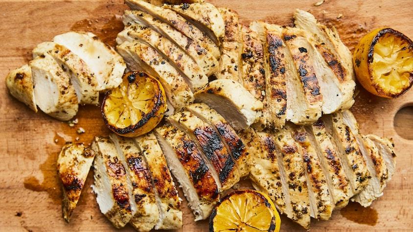 Poulet au citron grillé étalé sur une planche en bois.