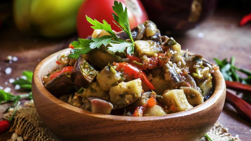 Un plat en bois rempli de ratatouille.