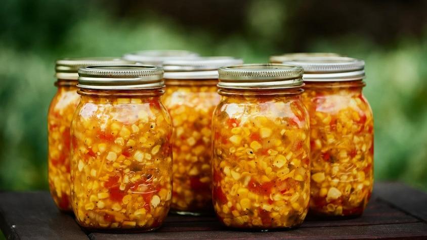 Plusieurs pots en vitre rempli de relish de maïs et de courgettes.