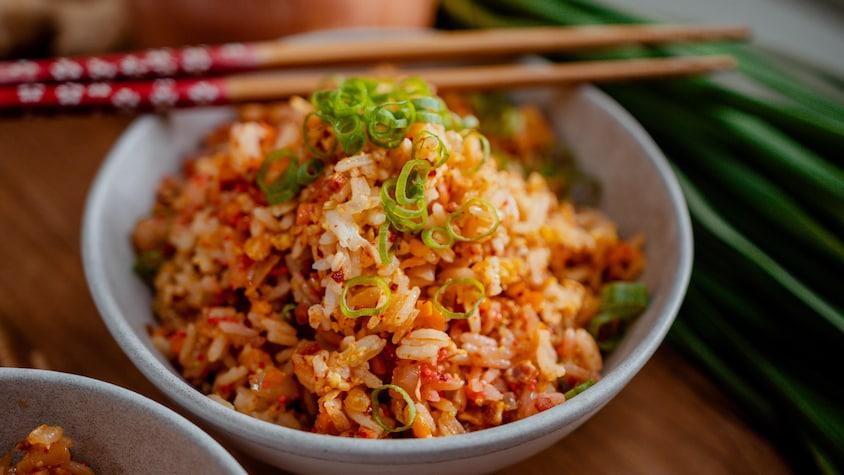 Un bol de riz frit, des baguettes.