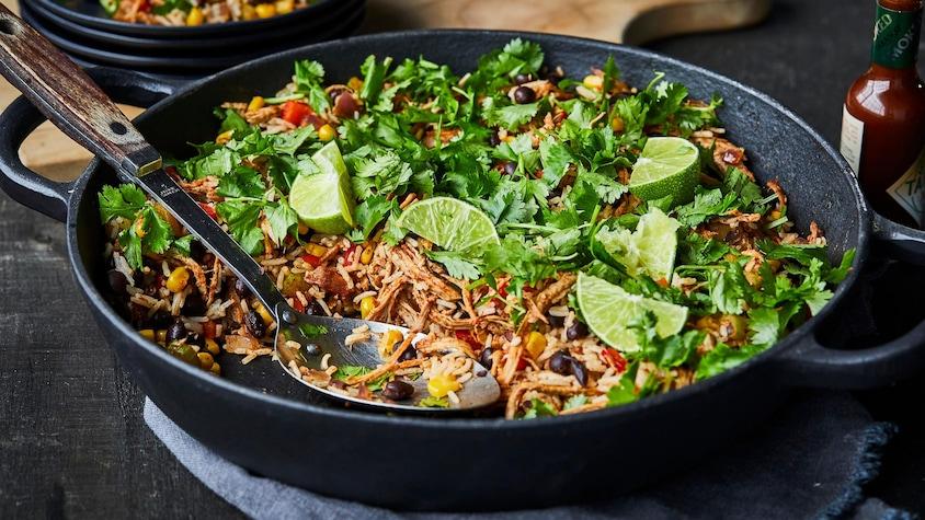 Grand plat rempli de riz mexicain effiloché avec coriandre et limes.