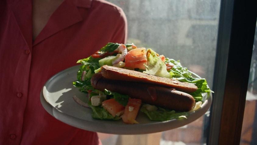 Une salade de légumes avec 2 saucisses sur une assiette.