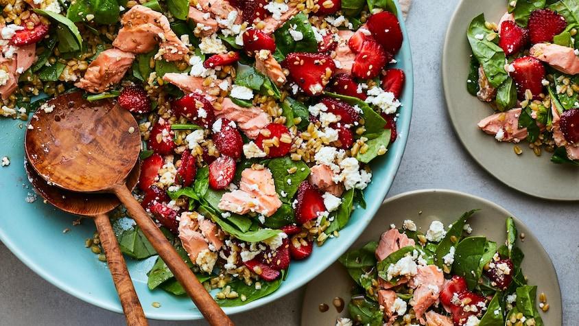 Un grand bol de salade de truite saumonée aux fraises et aux épinards et deux assiettes servies.