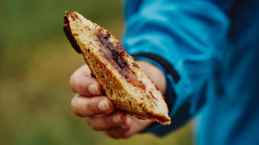 Il est possible de voir la main de Geneviève tenir un morceau de sandwich grillé.