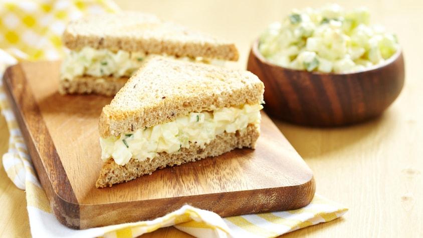 Un sandwich aux œufs coupé en deux sur une planche à découper.