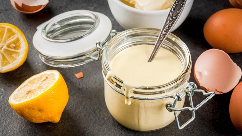 Un pot de sauce hollandaise avec du citron et des œufs tout autour.