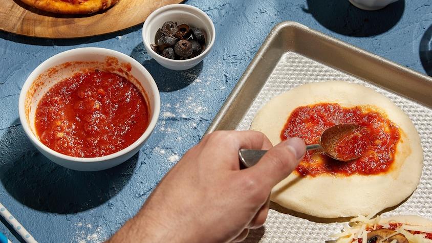 Un petit bol de sauce à pizza avec une pâte à pizza en train de se faire recouvrir de sauce.