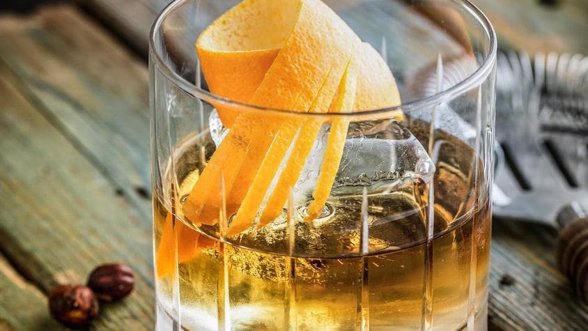 Un verre de scotch servi avec une écorce d'orange.
