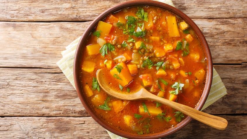 Un bol de soupe aux légumes avec une cuillère dedans.