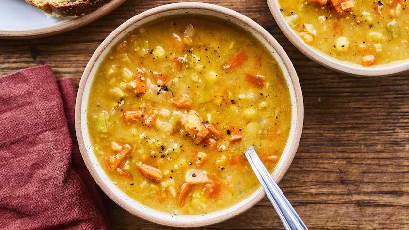 Un bol de soupe aux pois avec une cuillère dedans. À côté, une tranche de pain dans une assiette, un autre bol de soupe aux pois et une serviette de table.
