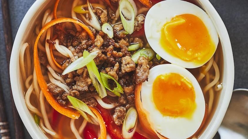 Un bol de ramen au porc caramélisé avec les deux œufs coulants sur le dessus.