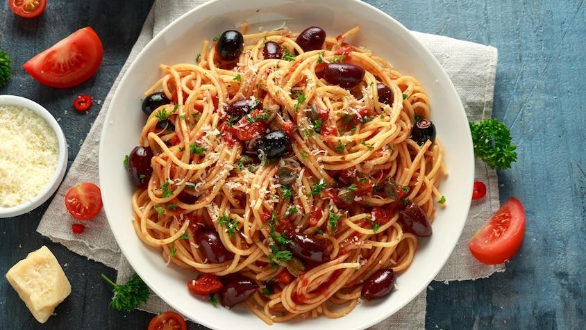 Des spaghettis recouverts de morceaux de tomates, d'olives, d'anchois et de persil.