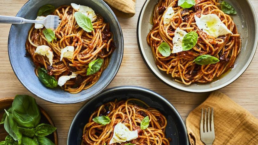 Bols de spaghetti aux tomates et au pesto posés sur une table en bois.