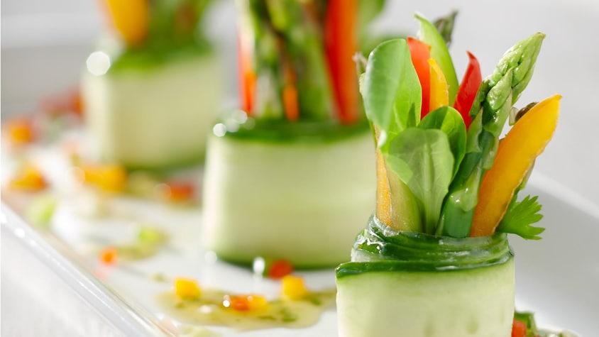 Une assiette avec trois roulés de concombre farcis d'asperges, de laitue, de poivrons et de fines herbes.