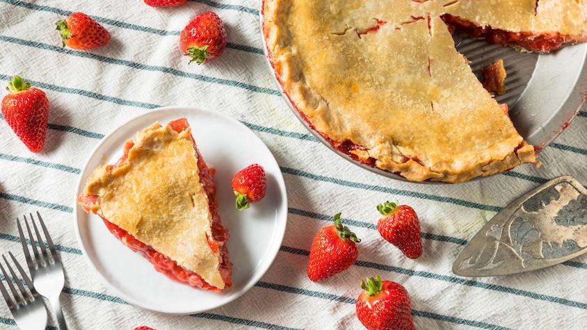 Une tarte aux fraises avec une part dans une petite assiette.