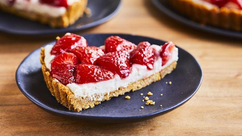 Une pointe de tarte Graham aux fraises dans une assiette.
