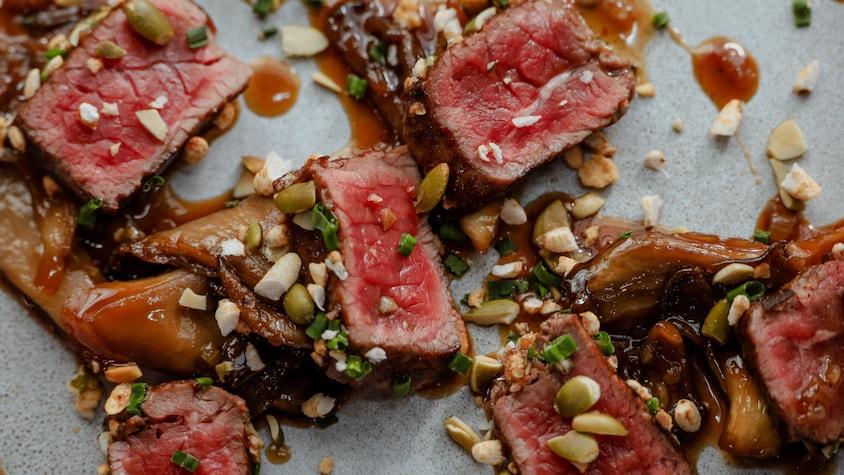 De fines lanières de bison en tataki, nappées de sauce à l'érable et garnies d'un mélange de noix et de fines herbes.