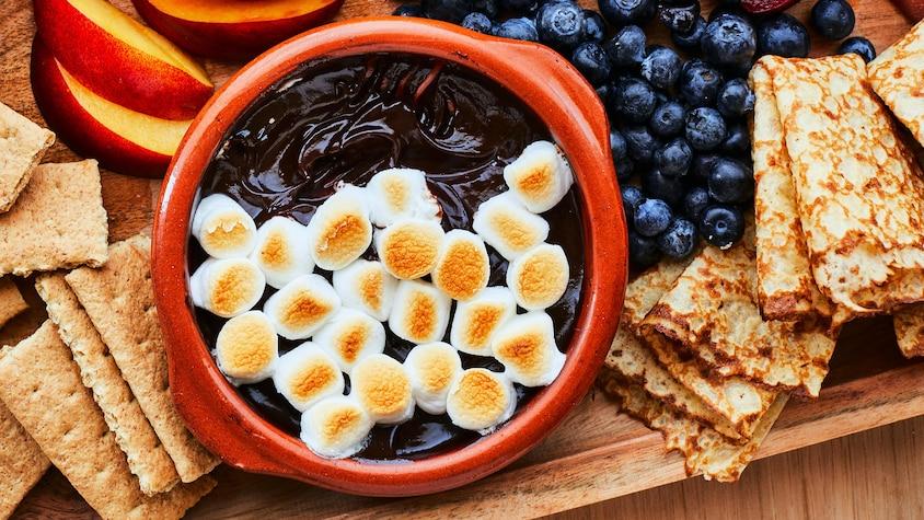 Au centre de l'image, est déposé un bol contenant la trempette s'mores. À l'entour, il y a des crêpes, bleuets, biscuits Graham et pêches.