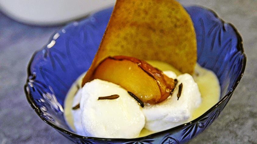 Un petit bol de crème glacée avec une tuile de riz sauvage en garniture.