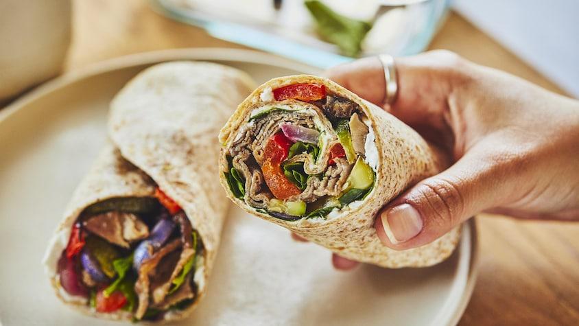 Wrap au bœuf et aux légumes grillés dans une assiette.